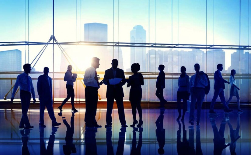 Silhouettes of business people collaborating in front of tall windows