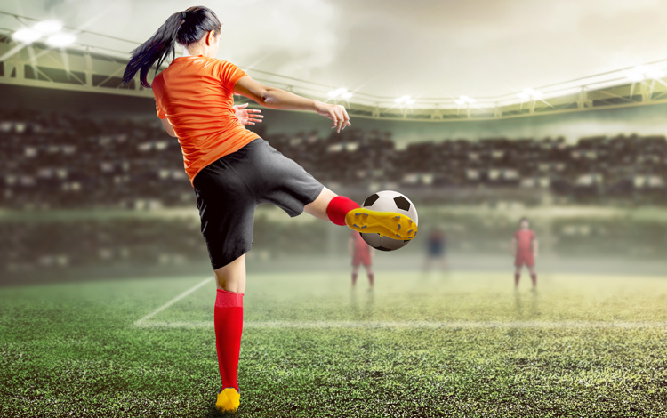 Woman volleying a football/soccer ball